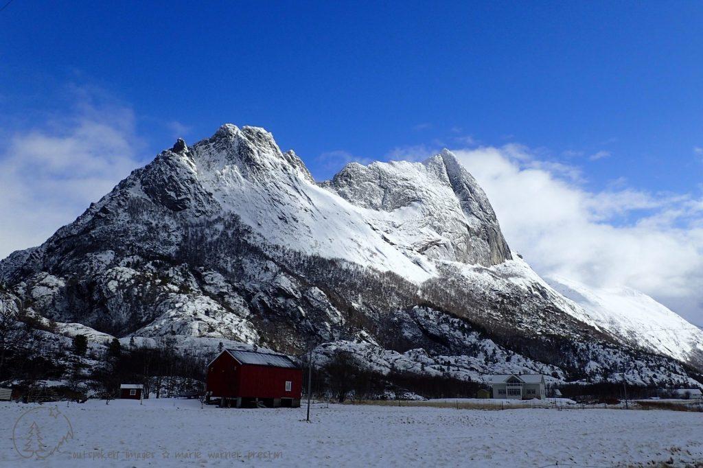 The mountain peak at Strandaa, Kjerringøy, Norway. grey rock with snow. House foreground