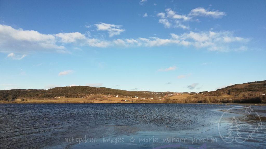 Randfjorden, Jevnaker, Norway. blue water, golden fields, blue sky with white clouds